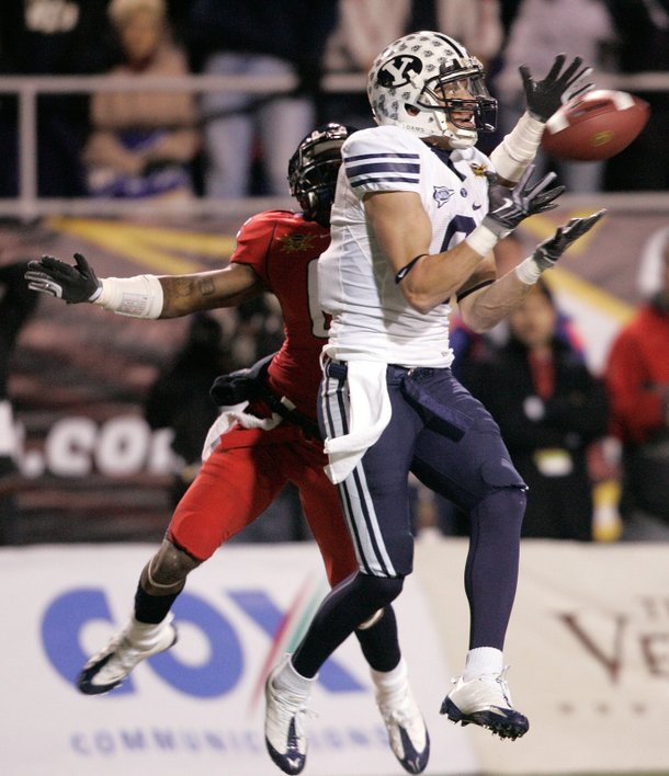 Austin Collie of BYU catches a pass while Devin Ross of the University of Arizona defends during the Las Vegas Bowl at Sam Boyd Stadium Saturday.