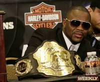 A dapperly dressed Rashad Evans takes questions at the post-fight press conference, next to his Light Heavyweight belt.