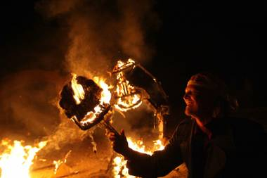 Sam Gurr, the creator of the three monster effigies, holds a flaming head aloft.
