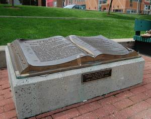This bronze book tells the history of Park Central Square in Springfield, Missouri, minus one important element, added in the form of a plaque on the front of the monument.