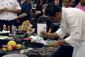 Kuldeep Singh of Origin India plates extra food for audience members to try.