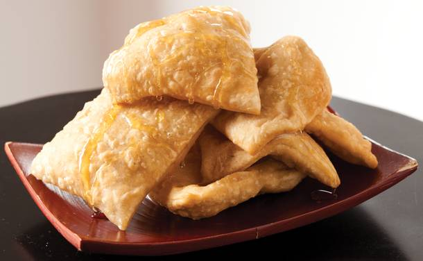 Sopapillas, a light, flaky dessert to be eaten with generous applications of butter and honey.