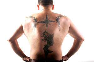 Geno Bernardo shows his tattoo artist father's work on his back.