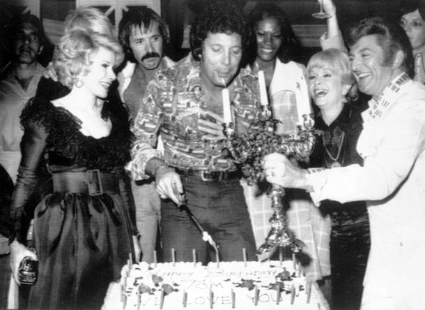 British singer Tom Jones, center, blows out candles at a surprise birthday party at Caesars Palace on June 6, 1974. Guests include Joan Rivers, Sonny Bono, Jones, Dionne Warwick, Debbie Reynolds and Liberace.