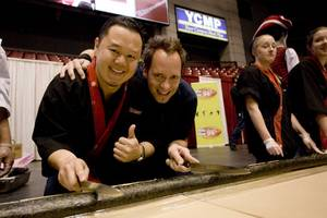 Jet and Kevin Brauch with the practice sushi roll for a Guinness Record attempt.