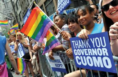 People hold signs thanking Governor Andrew Cuomo at the annual Heritage of Pride March, one of the world's oldest and largest gay pride parades, Sunday June 26, 2011, in New York.  The parade became a victory celebration after New York's historic decision to legalize same-sex marriage on Friday.
