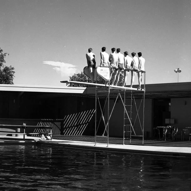 Spectators stand on a diving board to get a better view of a bomb detonation, circa 1953.