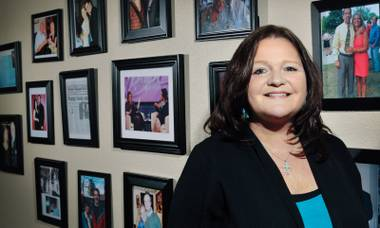 Wall of fame: Patti Novak's Vegas office is decorated with portraits of happy couples she's brought together (plus one of her and Oprah).