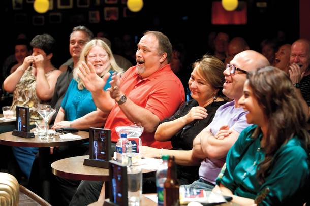 Audience members crack up laughing as comedians heckle front-row guests at Brad Garrett's Comedy Club.