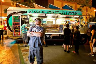 Vendor Manager Keith McCoy, who also manages the Slidin' Thru truck, monitors the flow of people filling the plaza during the Vegas StrEats Festival in Las Vegas Saturday night, August 10, 2013.